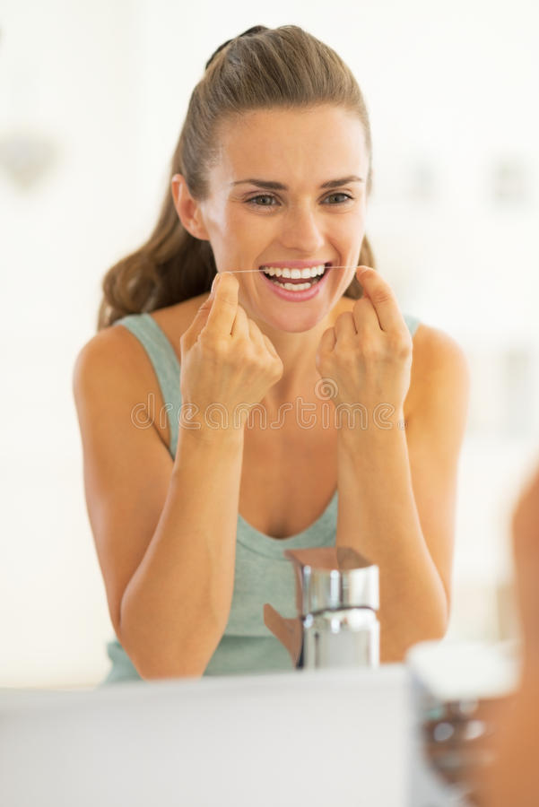 Young woman using dental floss in bathroom. Portrait of young woman using dental floss in bathroom royalty free stock images