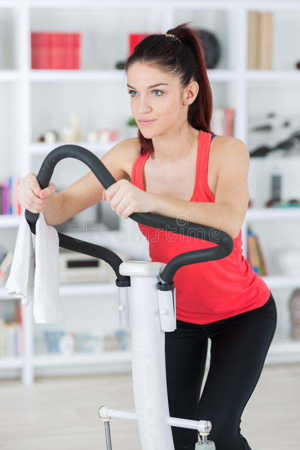 Young woman using exercise machine at home royalty free stock images