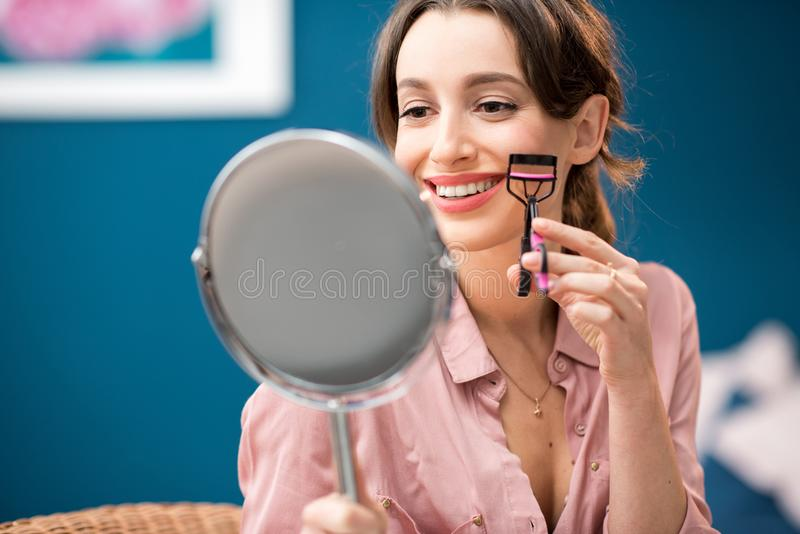 Woman using eyelash curler. Young woman using eyelash curler sitting with mirror on the blue wall background indoors stock photos