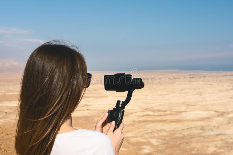 Young woman using gimbal in the desert of israel. Filming the desert lanscape with a phone and a gimbal. Dead sea in the background royalty free stock photography