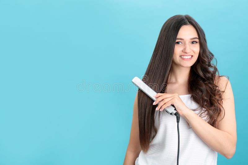 Young woman using hair iron on blue background, space for stock photos