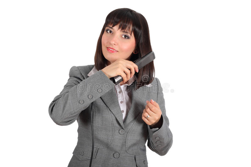 Young woman using hair straightener royalty free stock image