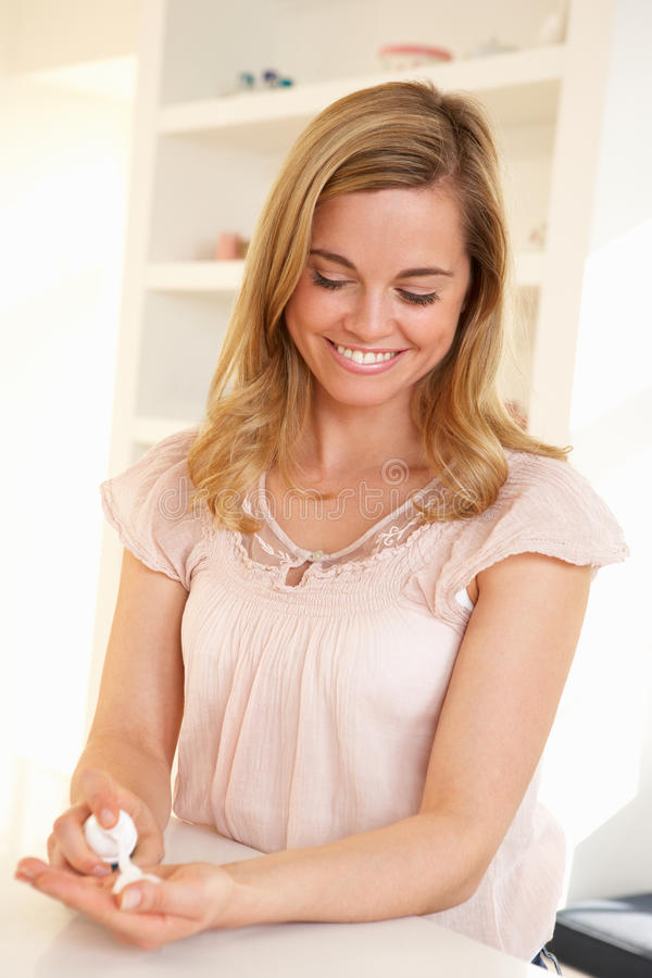 Young woman using hand sanitizer royalty free stock image