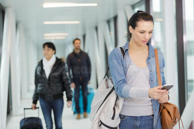 Young woman using cell phone at departure gate stock photo