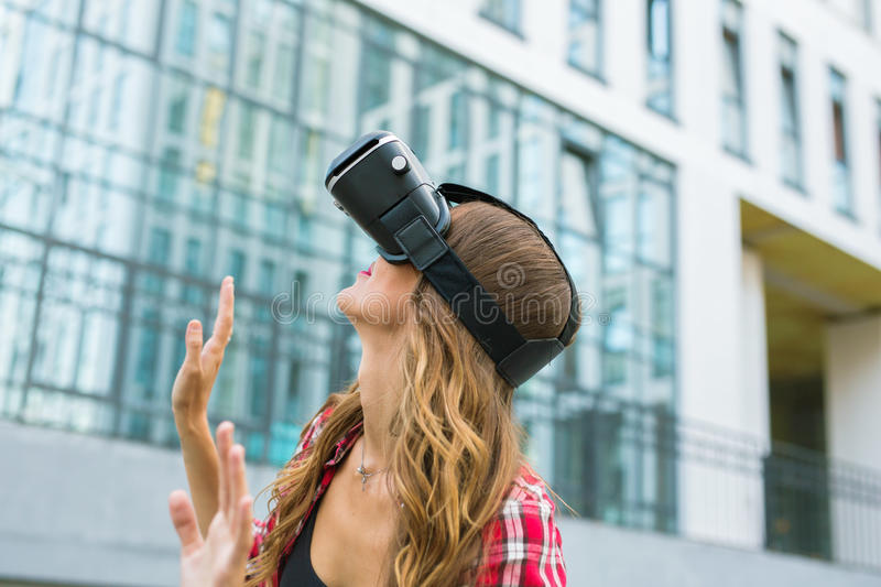 Young woman using high tech virtual reality glasses outdoor.  royalty free stock images