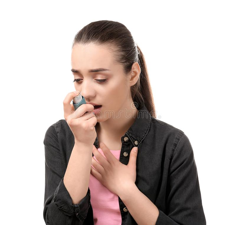 Young woman using inhaler on white background. Allergy concept stock photos