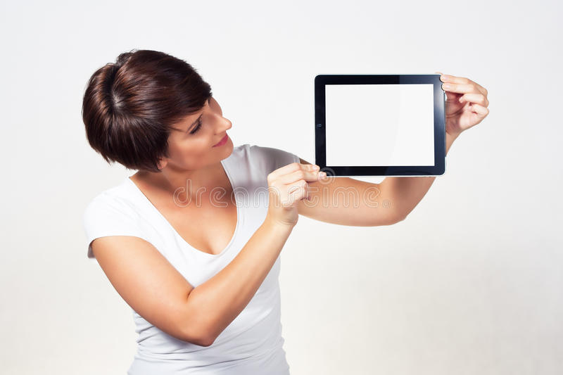 Young woman using iPad. Young woman showing a tablet