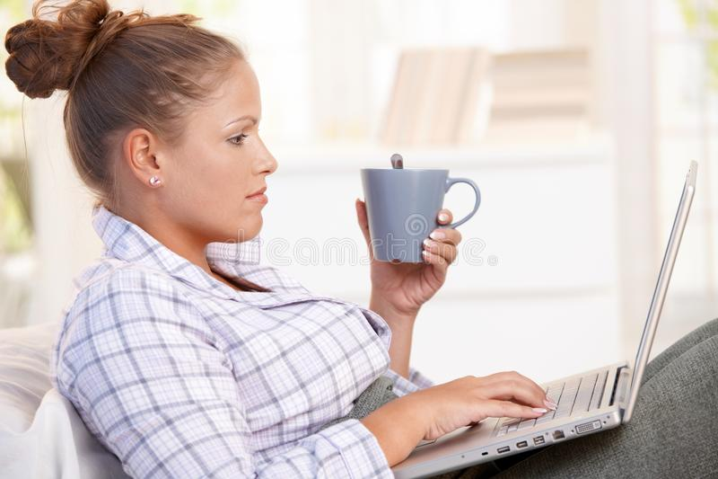 Young woman using laptop in bed drinking tea royalty free stock photography