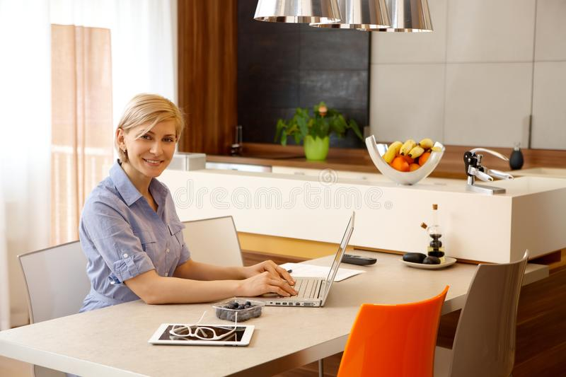 Young woman using laptop at home. Young woman using laptop computer at home, typing, smiling, looking at camera stock photo