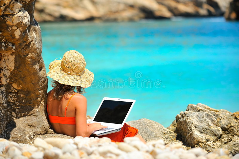 Young woman using laptop by the sea stock photo