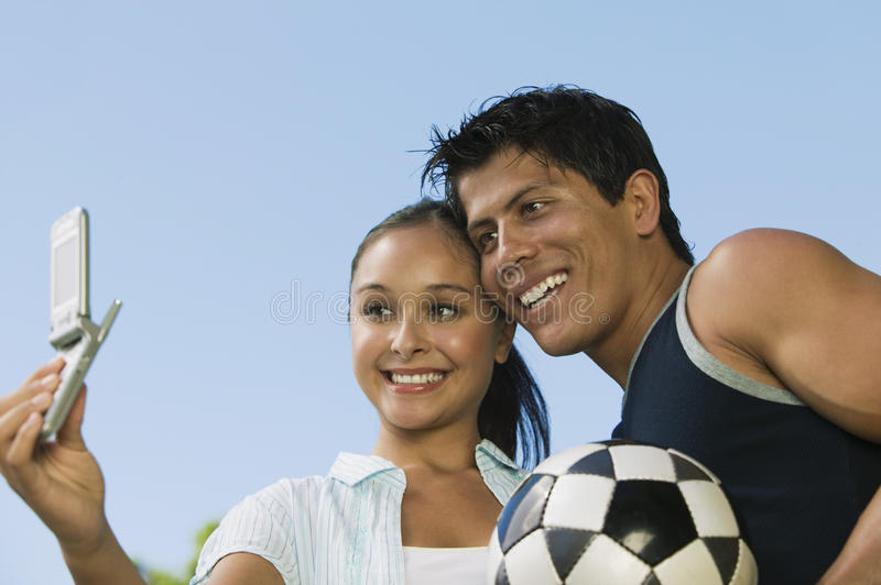 Young woman using mobile phone photographing self with young man. royalty free stock photos