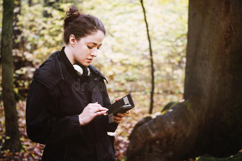 Young woman using mobile smart phone outdoors in forest stock images