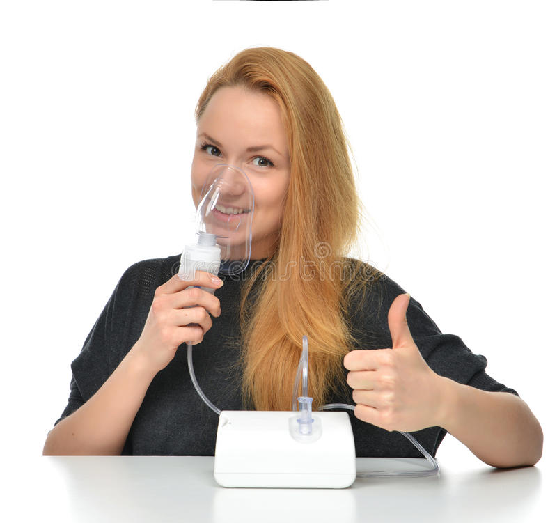 Young woman using nebulizer mask for respiratory inhaler Asthma. Treatment isolated on a white background stock photo
