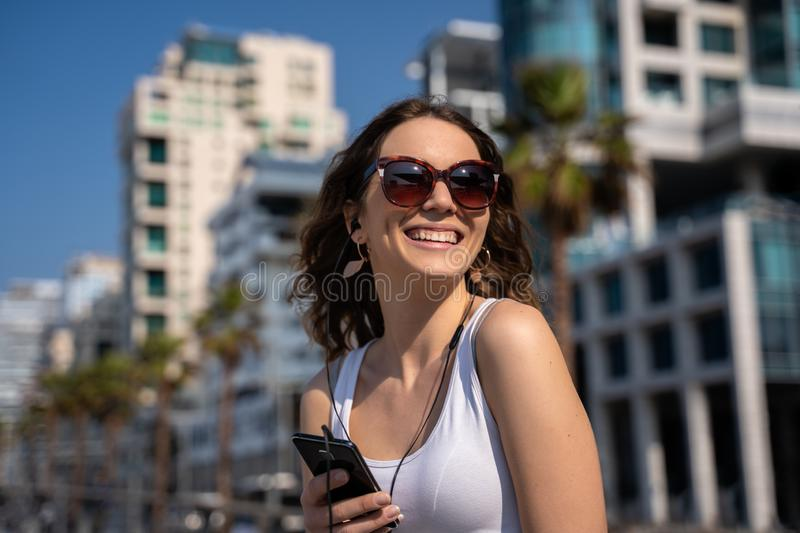 Young woman using the phone with headset. City Skyline In Background. Woman smiling and using a smartphone in the city, clear sky and tall buildings as royalty free stock photography