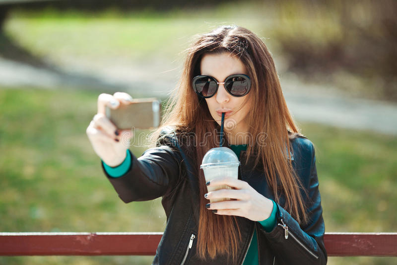 Young woman using a phone makes selfie royalty free stock images