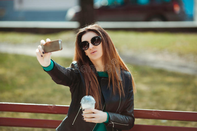 Young woman using a phone makes selfie stock photography
