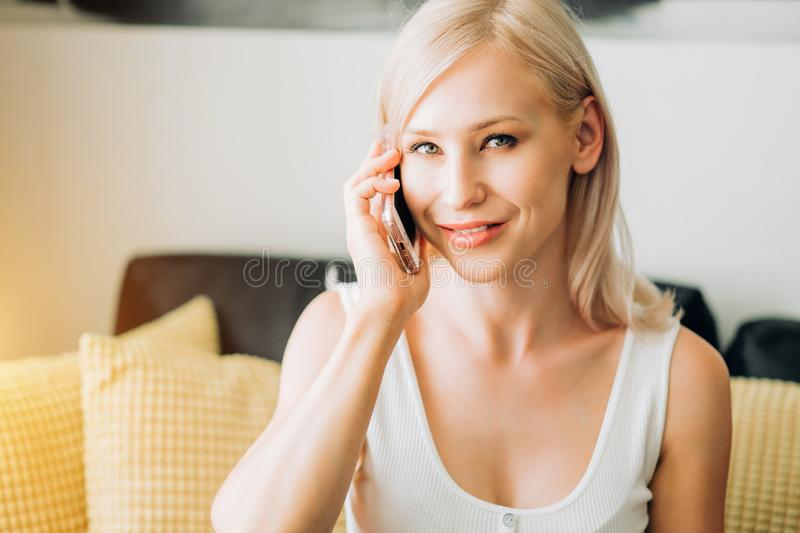 Young woman using phone while relaxing on sofa stock photography