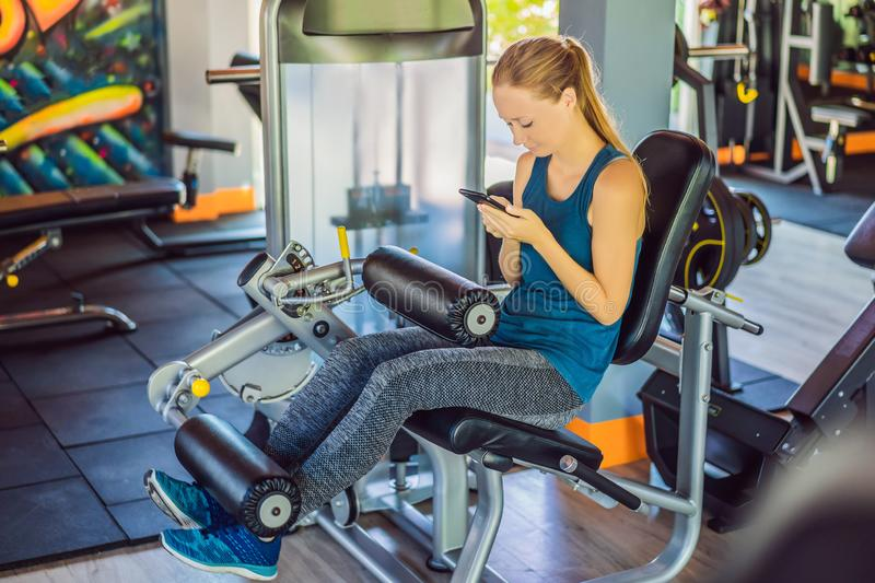 Young woman using phone while training at the gym. Woman sitting on exercising machine holding mobile phone royalty free stock image