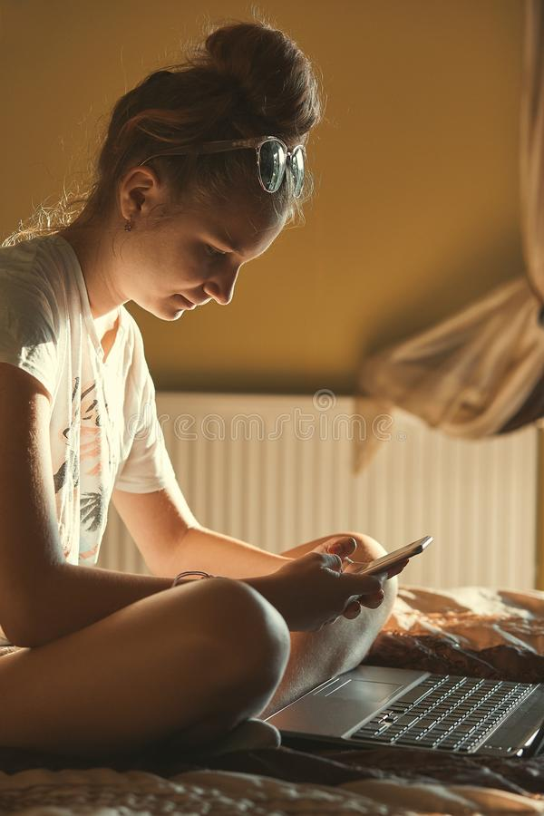 Young woman using portable computer and mobile phone. Sitting on a bed, learning online at home. Candid people, real moments, authentic situations stock images