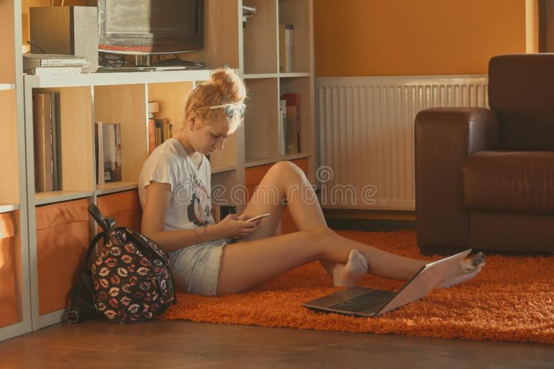 Young woman using portable computer and mobile phone. Sitting on a floor, learning online at home. Candid people, real moments, authentic situations royalty free stock photo