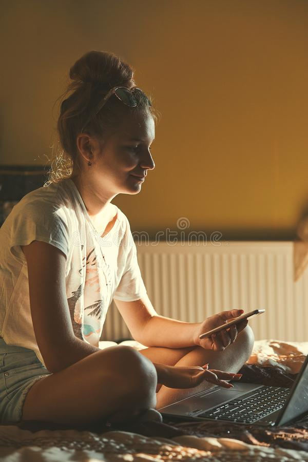 Young woman using portable computer and mobile phone. Sitting on a bed, learning online at home. Candid people, real moments, authentic situations royalty free stock image