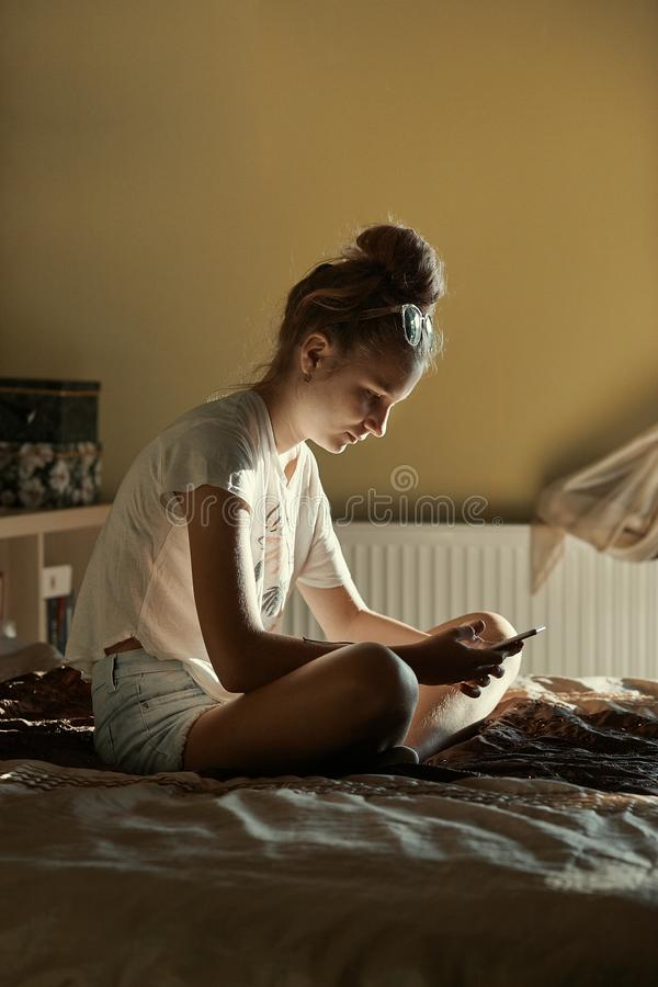 Young woman using portable computer and mobile phone. Sitting on a bed, learning online at home. Candid people, real moments, authentic situations royalty free stock photo