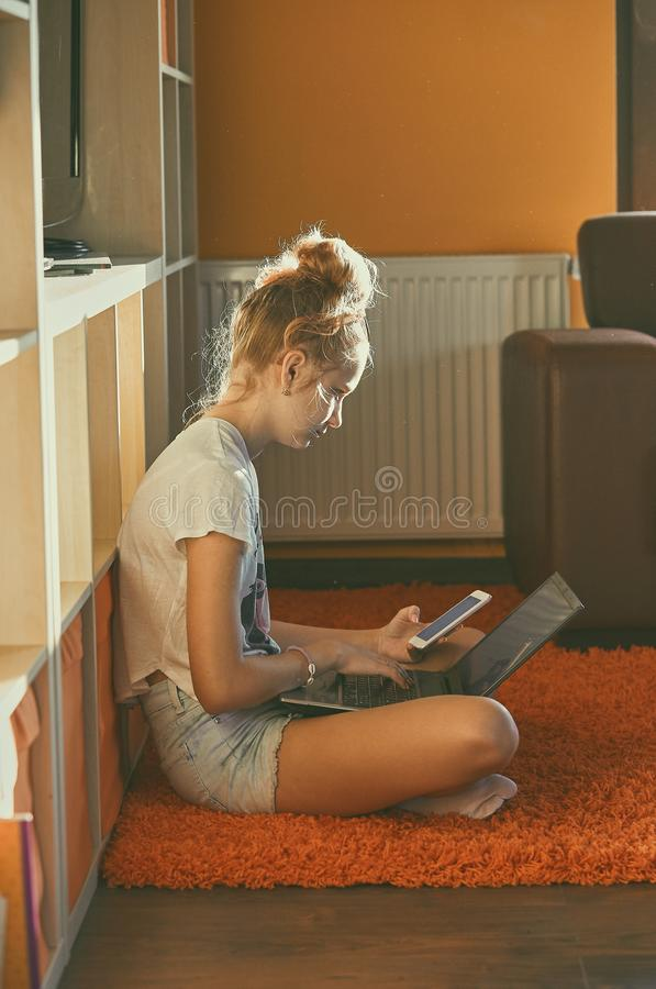 Young woman using portable computer and mobile phone. Sitting on a floor, learning online at home. Candid people, real moments, authentic situations stock photos