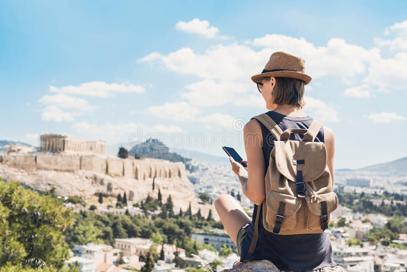 Young woman using smart phone in Athens with Acropolis at the background. Traveler girl enjoying vacation in Greece. royalty free stock image