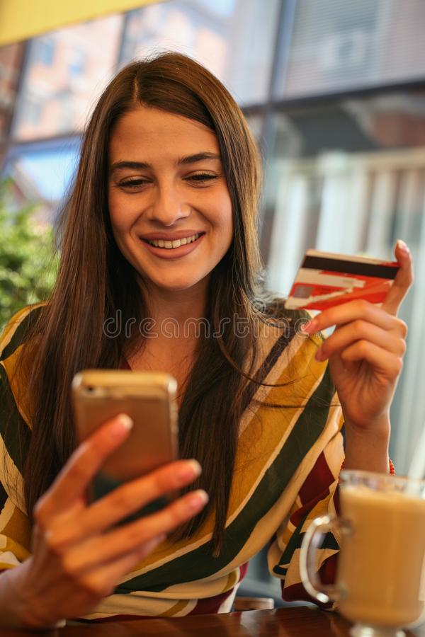 Young woman using smart phone and credit card. Woman shopping trough credit card royalty free stock photo
