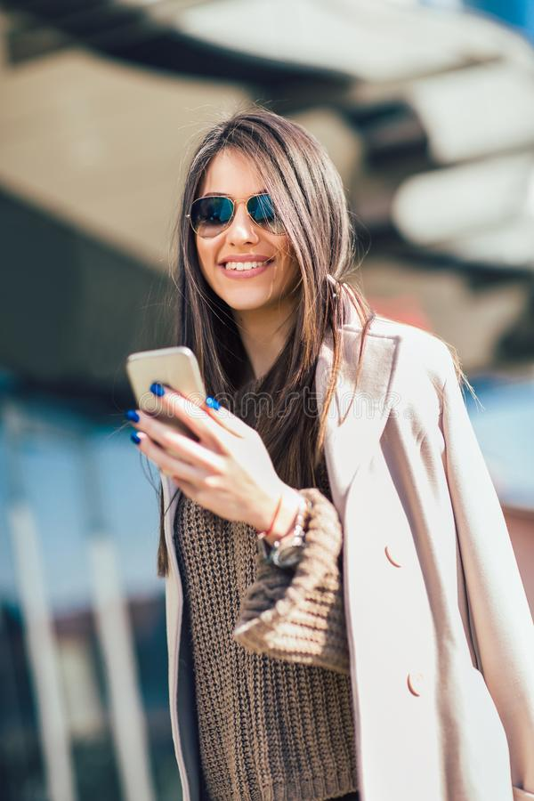 Woman using smart phone outdoors stock images