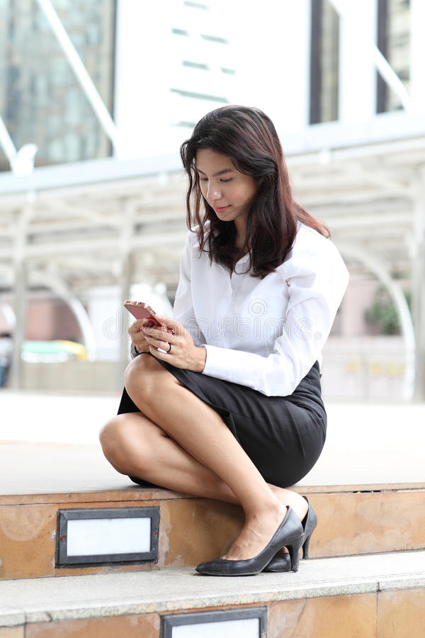 Young Woman Using A Smart Phone Standing Outdoors Reading A Text Stock Photos