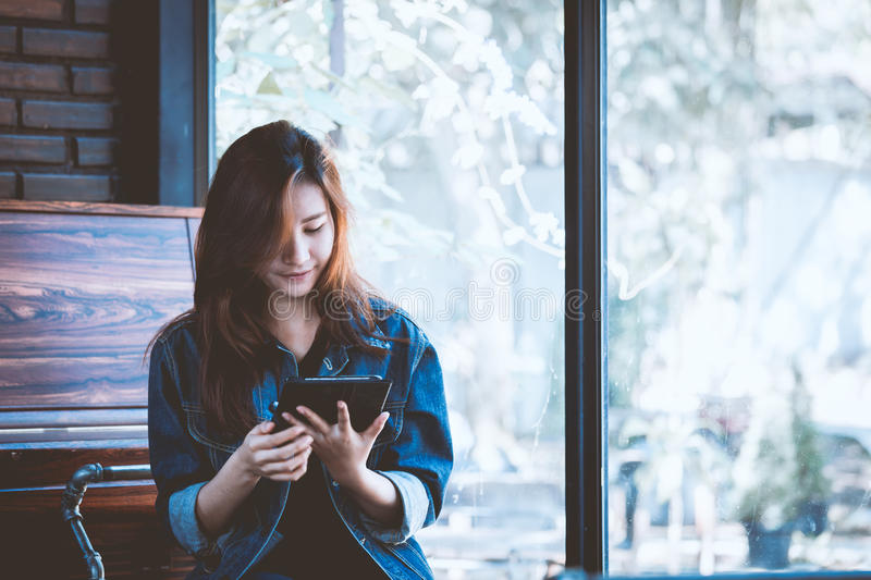 Young woman using tablet in coffee shop. Hipster girl in cafe. royalty free stock images