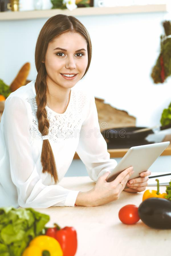 Young woman using tablet while cooking or making online shopping in kitchen. Girl looking at the camera. Healthy. Lifestyle and vegan meal concepts stock photos