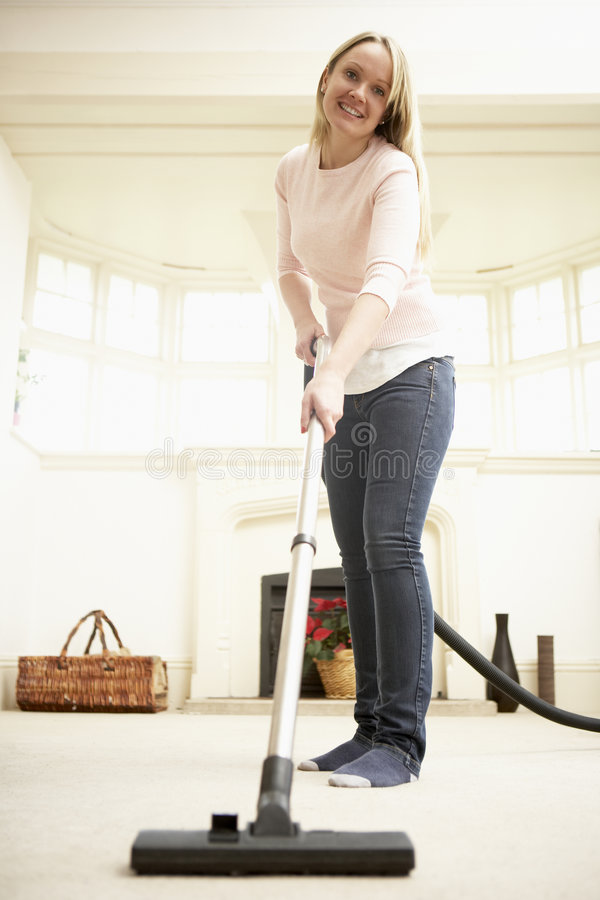 Young Woman Using Vacuum Cleaner stock images