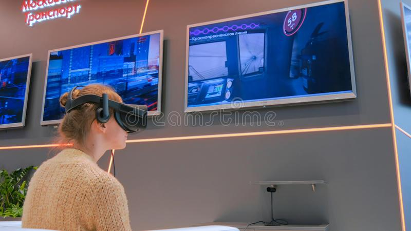 Young woman using virtual reality glasses. MOSCOW, RUSSIA - July 30, 2018: Moscow Urban Forum. Virtual reality game. Young woman using virtual reality headset royalty free stock images