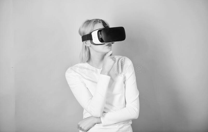 Young woman using a virtual reality headset. Happy woman exploring augmented world, interacting with digital interface royalty free stock photography