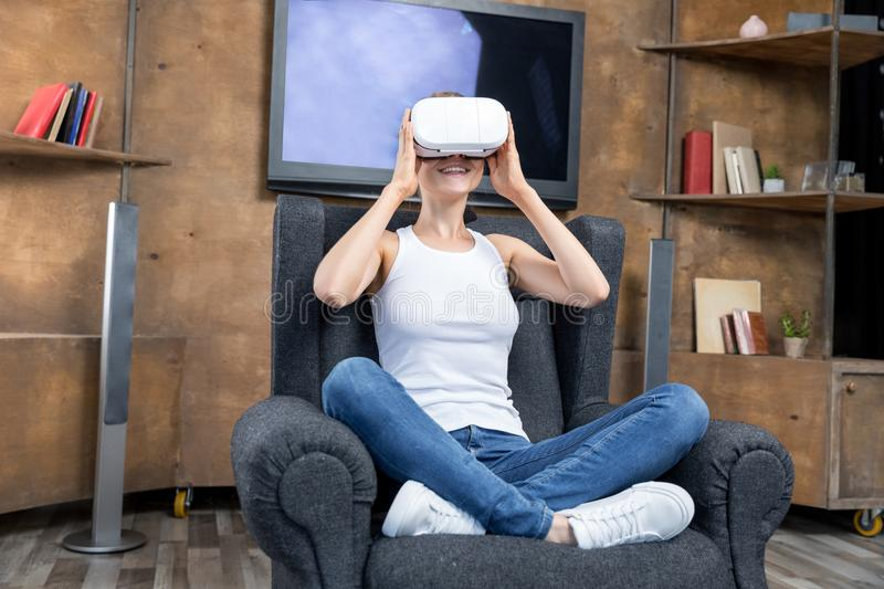 Young woman using virtual reality headset while sitting in gray armchair royalty free stock image
