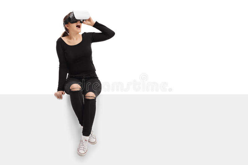Young woman using virtual reality headset and sitting on panel royalty free stock image