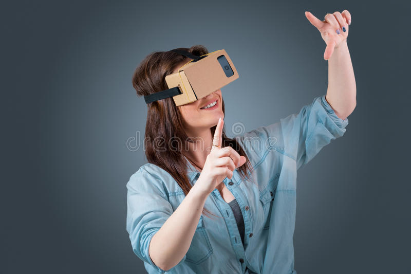 Young woman using a VR headset glasses. Excited young woman using a VR headset glasses and experiencing virtual reality on grey blue background stock images