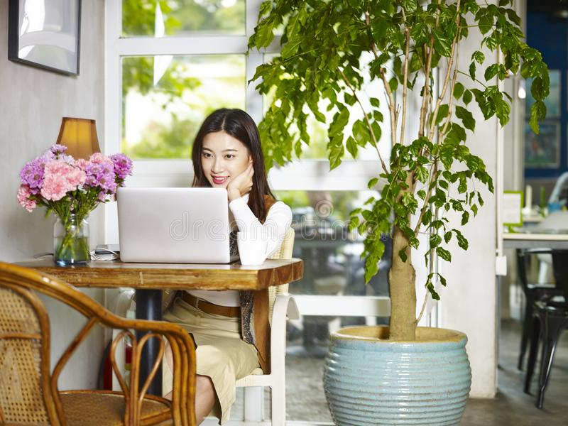 Young woman using working with laptop in coffee shop stock photo