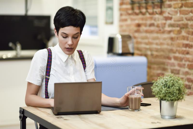 Young woman with very short haircut typing with a laptop at home royalty free stock photos
