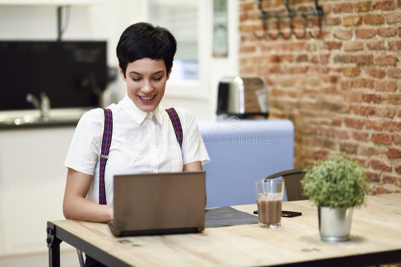 Young woman with very short haircut typing with a laptop at home. stock photo