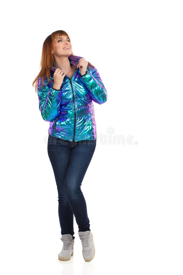 Young woman in vibrant and shiny down jacket, jeans and sneakers is standing, looking away and smiling. Front view. Full length royalty free stock photos