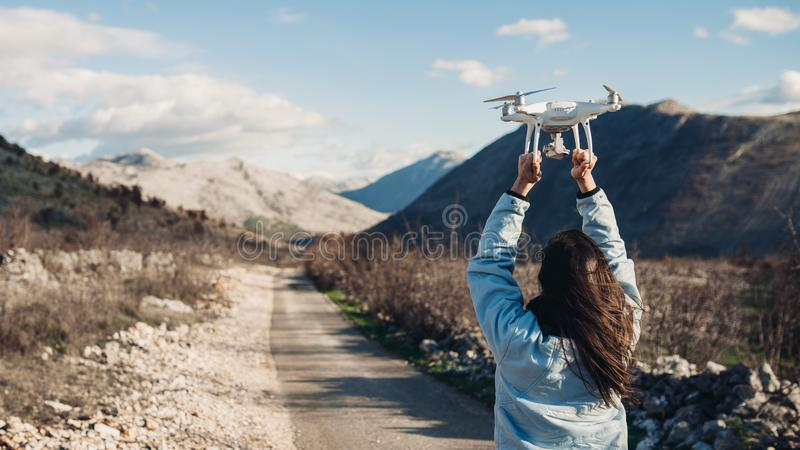 Young woman videographer catching flying aircraft with camera.Controlling landing of drone.Female filmmaker in nature royalty free stock image