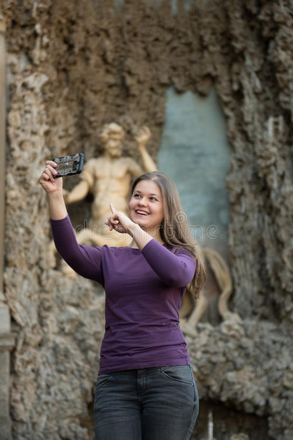 Woman in Villa Aldobrandini, Italy. Young woman in Villa Aldobrandini, Frascati, Italy, in front of antique fontain, maked selfie photos with smartphone stock photos