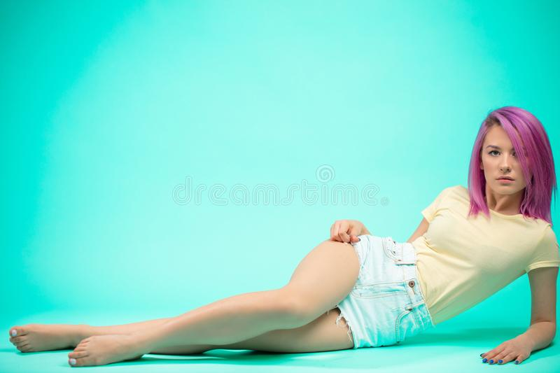 Young woman with villet hairstyle sitting on the floor isolated royalty free stock photo