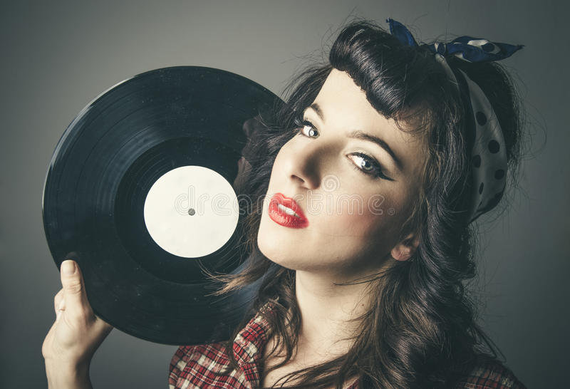 Young woman in vintage clothes with vinyl record stock photo