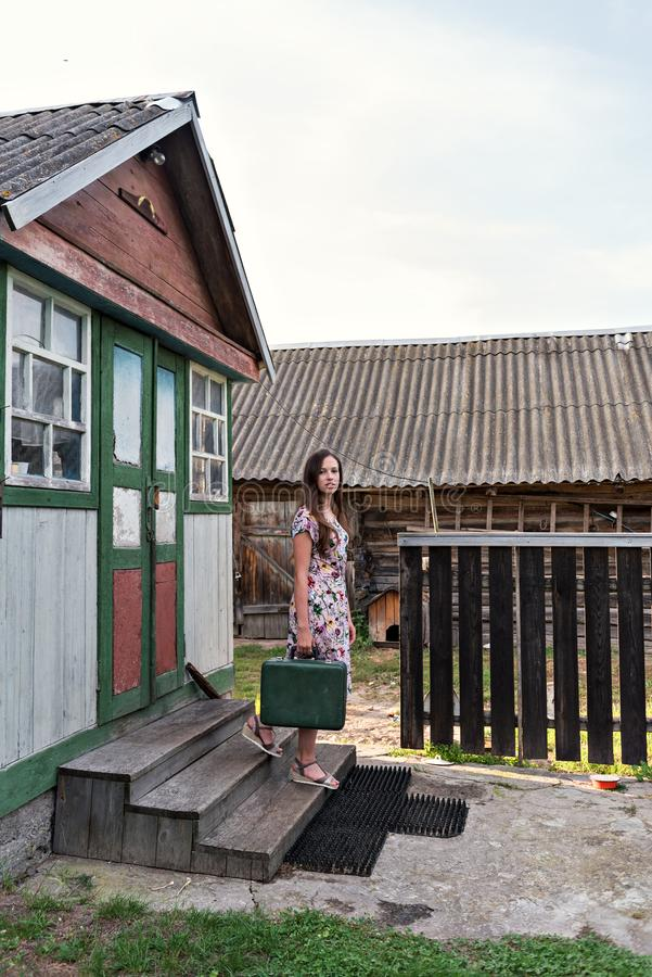 A young slender woman in a vintage dress descends the steps from a village shabby house to a country yard with sheds holding an. A young woman in a vintage dress stock photography