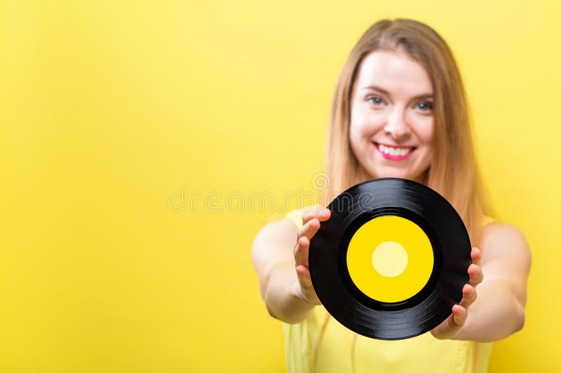 Young woman with a vinyl record. Young woman with a vintage vinyl record on a yellow background royalty free stock photos