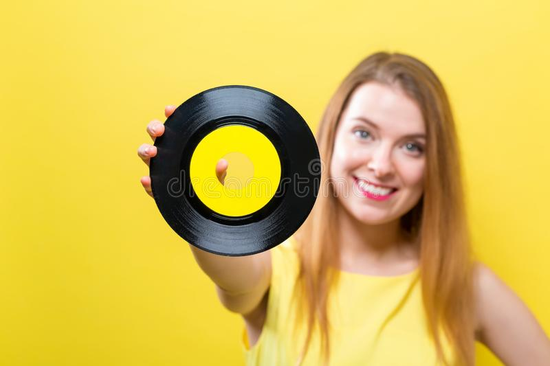 Young woman with a vinyl record. Young woman with a vintage vinyl record on a yellow background royalty free stock image